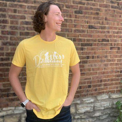 Male wearing yellow Driftless Journeys tee